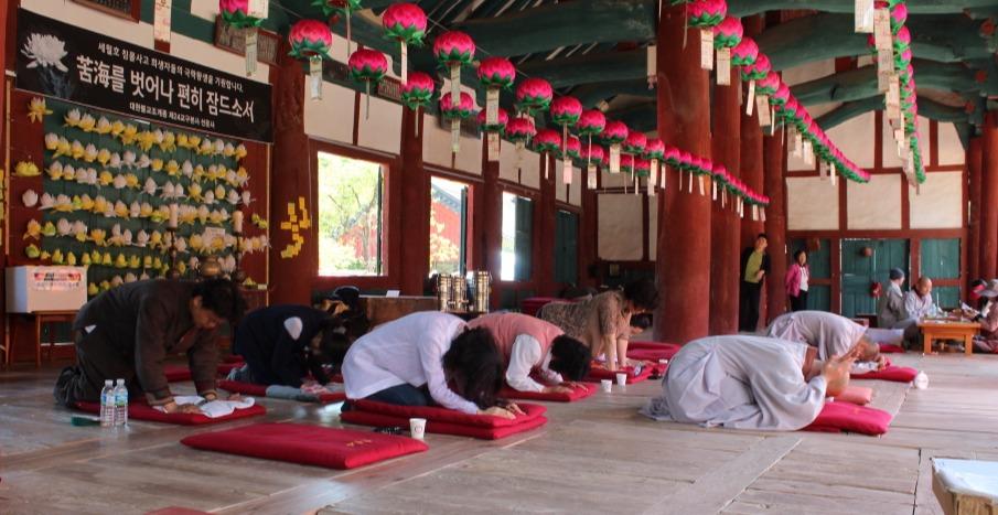 고창군종합사회복지시설 직원들이 지난 5월 부처님오신날을 맞아 선운사 만세루에서 스님들의 지도를 받아 절 기도를 하고 있다.