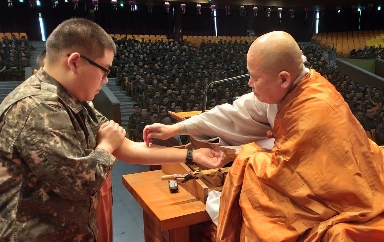 논산 육군훈련소 호국연무사 수계법회에서 훈련병에게 수계하는 군종교구장 선묵스님.