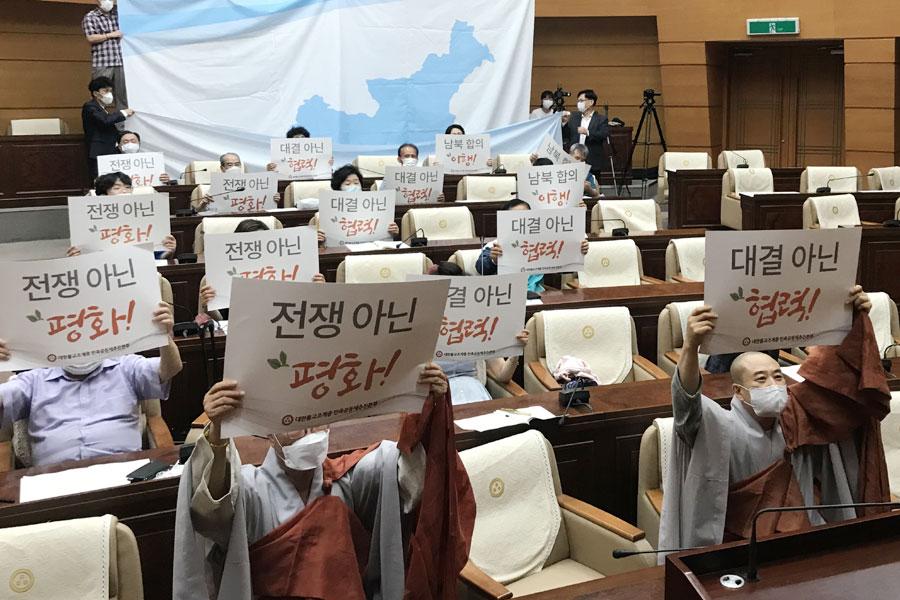 조계종 민족공동체추진본부가 개최한 남북 정세 토론회에서 참가자들이 손피켓을 들고 남북위기 극복을 기원하고 있다.
