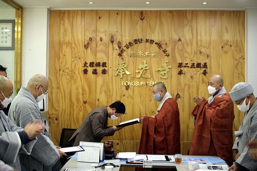 제25교구본사 봉선사 주지 초격스님이 교구전문기자 임명장을 수여하고 있다.