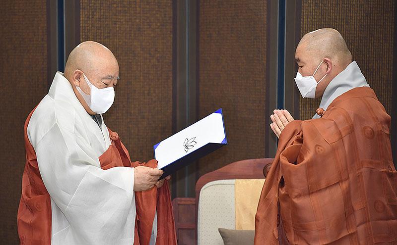조계종 총무원장 원행스님(왼쪽)이 민추본 본부장 월우스님에게 임명장을 전달하고 있다.